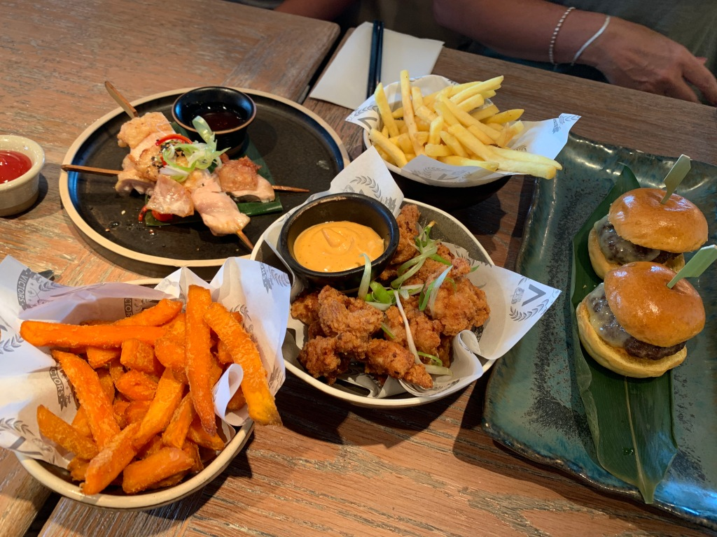 The dishes at Victors, a selection of meat small plates consisting of sweet potato fries, chicken skewers, popcorn chicken, Victors fries and lil' burgers.